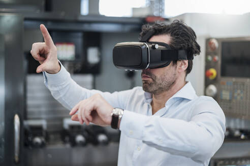 Businessman using VR glasses in a factory - DIGF09061