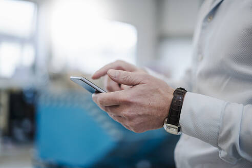 Close-up of businessman using cell phone in a factory - DIGF09076