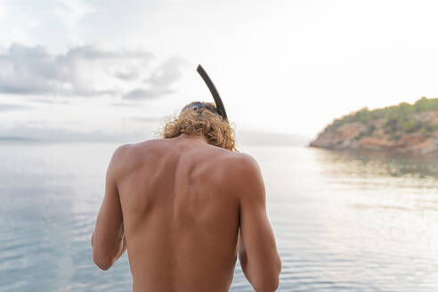 Rear view of young man with snorkel on beach - AFVF04977