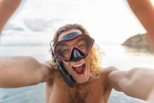 Young man with snorkel making a face on the beach - AFVF04980