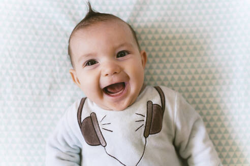 Portrait of laughing baby girl with appliqued headphones on pyjama - GEMF03396