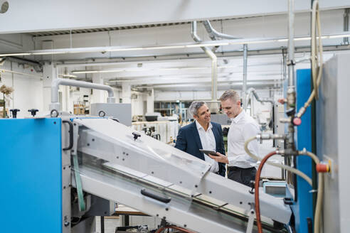 Two businessmen with tablet talking in a factory - DIGF09170