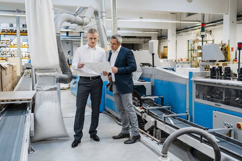 Two businessmen discussing paper in a factory - DIGF09179