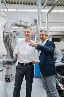 Two happy businessmen with paper talking in a factory - DIGF09182