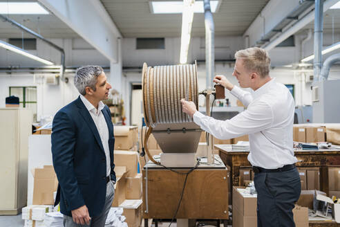 Two businessmen talking in a factory - DIGF09188