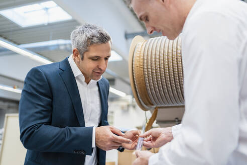 Two businessmen examining product in a factory - DIGF09191