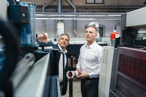 Two businessmen talking in a factory - DIGF09197