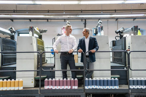 Two businessmen talking in a printing shop - DIGF09206