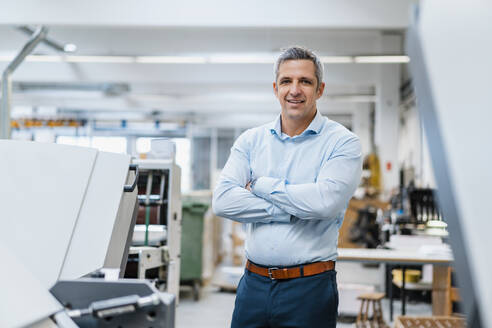 Portrait of a confident businessman in a factory - DIGF09236
