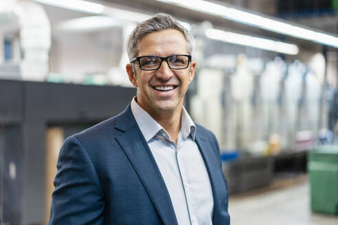 Portrait of a smiling businessman with glasses in a factory - DIGF09284
