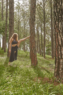 Barefoot young woman doing stretching exercise in the woods - VEGF01306