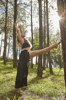 Barefoot young woman doing stretching exercise in the woods - VEGF01309