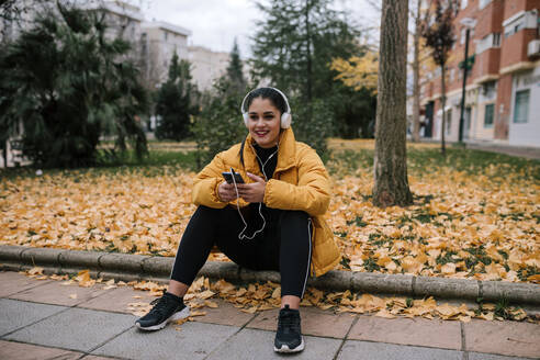 Portrait of smiling young woman  listening music with headphones and smartphone in autumn - GRCF00023