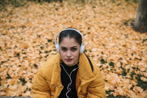 Portrait of young woman listening music with headphones in autumn - GRCF00026
