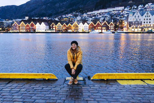 Woman wearing a yellow jacket and sitting at harbour in Bergen, Norway - DGOF00006