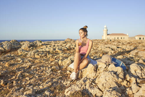 Young woman sitting on rocky beach, relaxing, Menorca, Spain - EPF00644