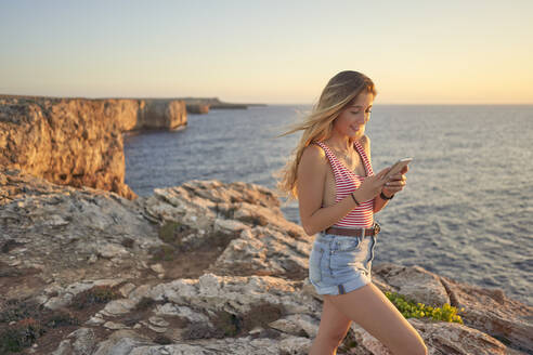 Young woman standing on cliff at the sea, using smartphone - EPF00650