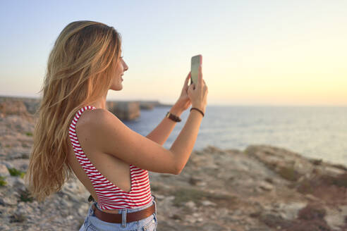 Young woman standing on cliff at the sea, using smartphone - EPF00653