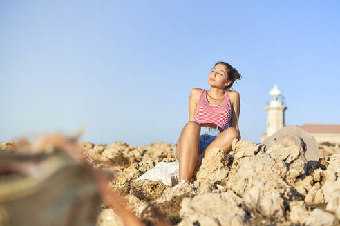 Young woman sitting on rocky beach, relaxing, Menorca, Spain - EPF00662