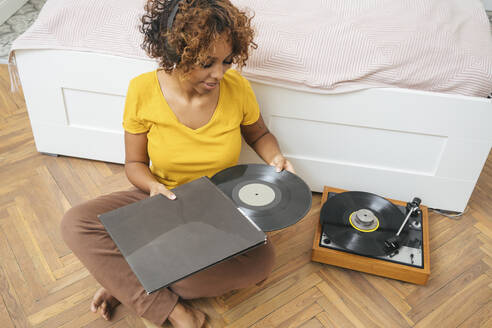 Young woman listening to music with headphones and record player at home - VPIF01929