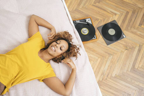 Young woman lying on bed listening to music with headphones and record player - VPIF01932