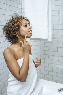 Young woman in bathroom applying face cream - VPIF01995