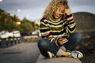 Portrait of woman wearing colorful pullover and using smartphone, Tenerife, Spain - SIPF02106