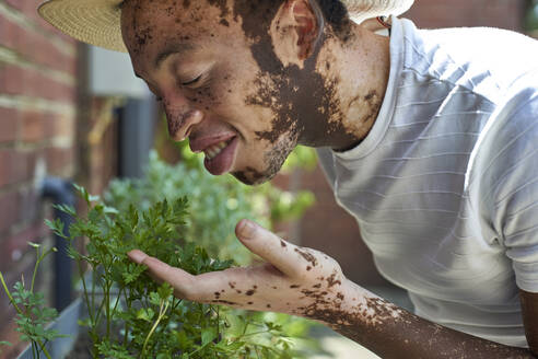 Young man with vitiligo with a hat smelling the plants - VEGF01330