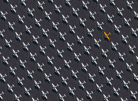 Aerial view of single orange colored airplane surrounded by exclusively white ones - KNTF04124