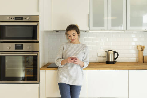 Young woman using smartphone at home - JPTF00397
