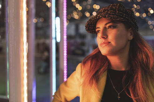 Portrait of woman with lights in the city at night - WPEF02436