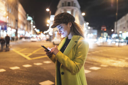 Woman with her smartphone in the city at night next to a road - WPEF02445