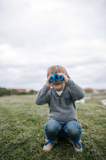 Smiling little boy crouching on a meadow looking through blue binoculars - GRCF00041