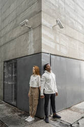 Man and woman leaning on a wall, security cameras hanging over their heads - AFVF04997