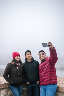 Young Mexican friends taking a selfie on a foggy day,  Toledo, Spain - GRCF00049