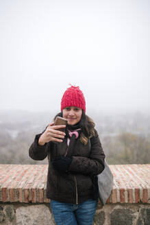 Young Mexican woman with wool hat taking a selfie on a foggy day - GRCF00052