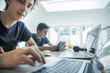 Two teenage boys using laptop and tablet on table at home - AJOF00082