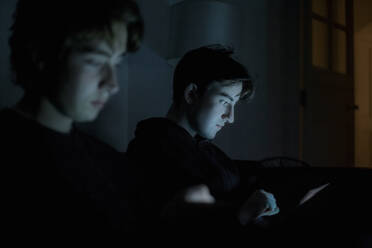 Two teenage boys using technology at home in the dark - AJOF00085