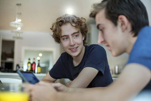 Smiling young man looking at friend using smartphone at home - AJOF00088
