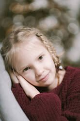Portrait of blond little girl wearing ruby knit pullover at home - EYAF00798