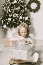 Portrait of blond little girl sitting in front of Christmas tree opening Christmas present - EYAF00804