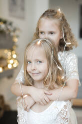 Portrair of little blond girl decorated with fairy lights - EYAF00807