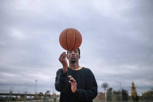 Teenager balancing basketball on his finger - GRCF00054
