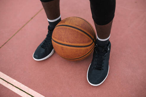 Basketball between feet of basketball player - GRCF00057