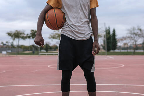 Teenager holding basketball with his arm - GRCF00066