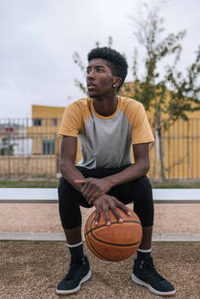 Teenager holding basketball and looking sideways - GRCF00072