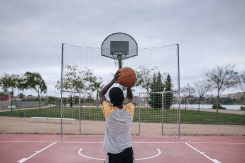 Rear view of teenager playing basketball - GRCF00075