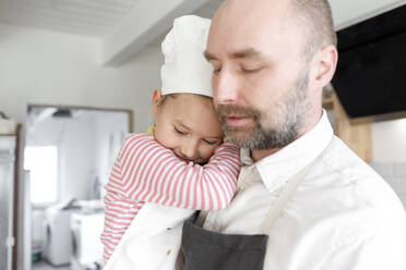 Father and daughter cooking in the kitchen - KMKF01162