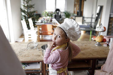Girl wearing chef's hat in the kitchen - KMKF01165