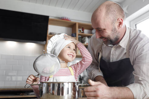 Father and daughter cooking in the kitchen - KMKF01168